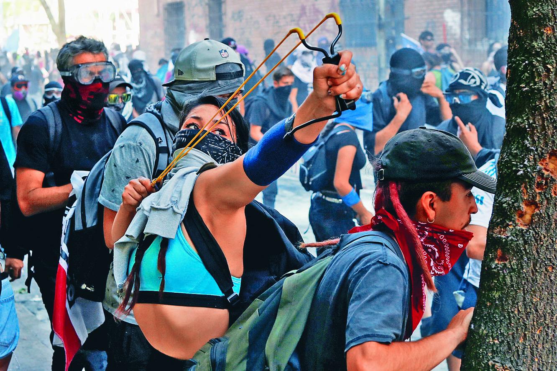 ■在智利首都聖地亞哥周 四的反政府示威中,一名 示威者使用彈弓。 路透社