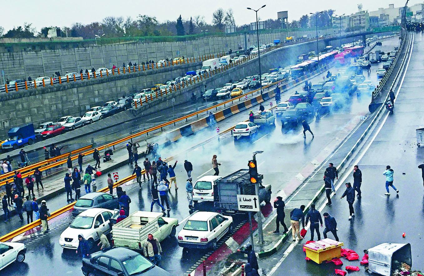 伊朗首都德黑蘭一條高速公路昨日有民眾示威, 抗議汽油價大漲,防暴警察發射催淚氣。 路透社