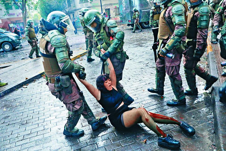 聖地亞哥警員周一拘捕一名受傷女示威者。路透社