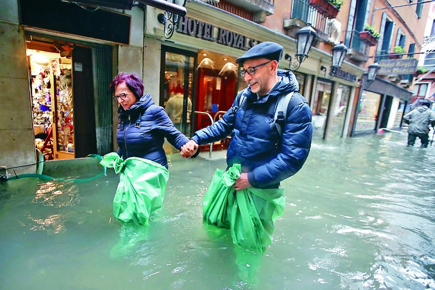■遊客在威尼斯街道涉水而行。 美聯社
