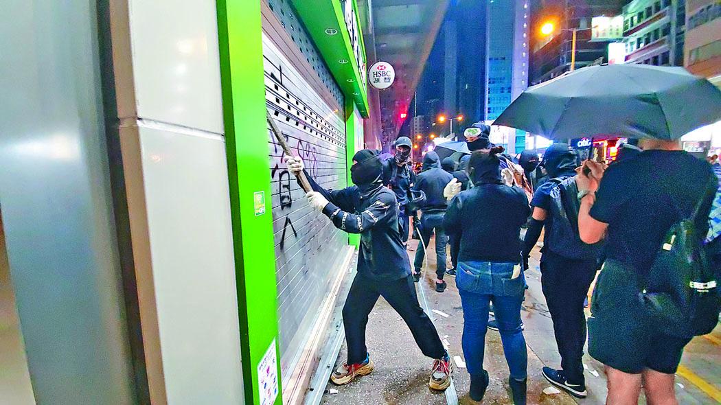 示威者向店鋪閘門進行破壞。