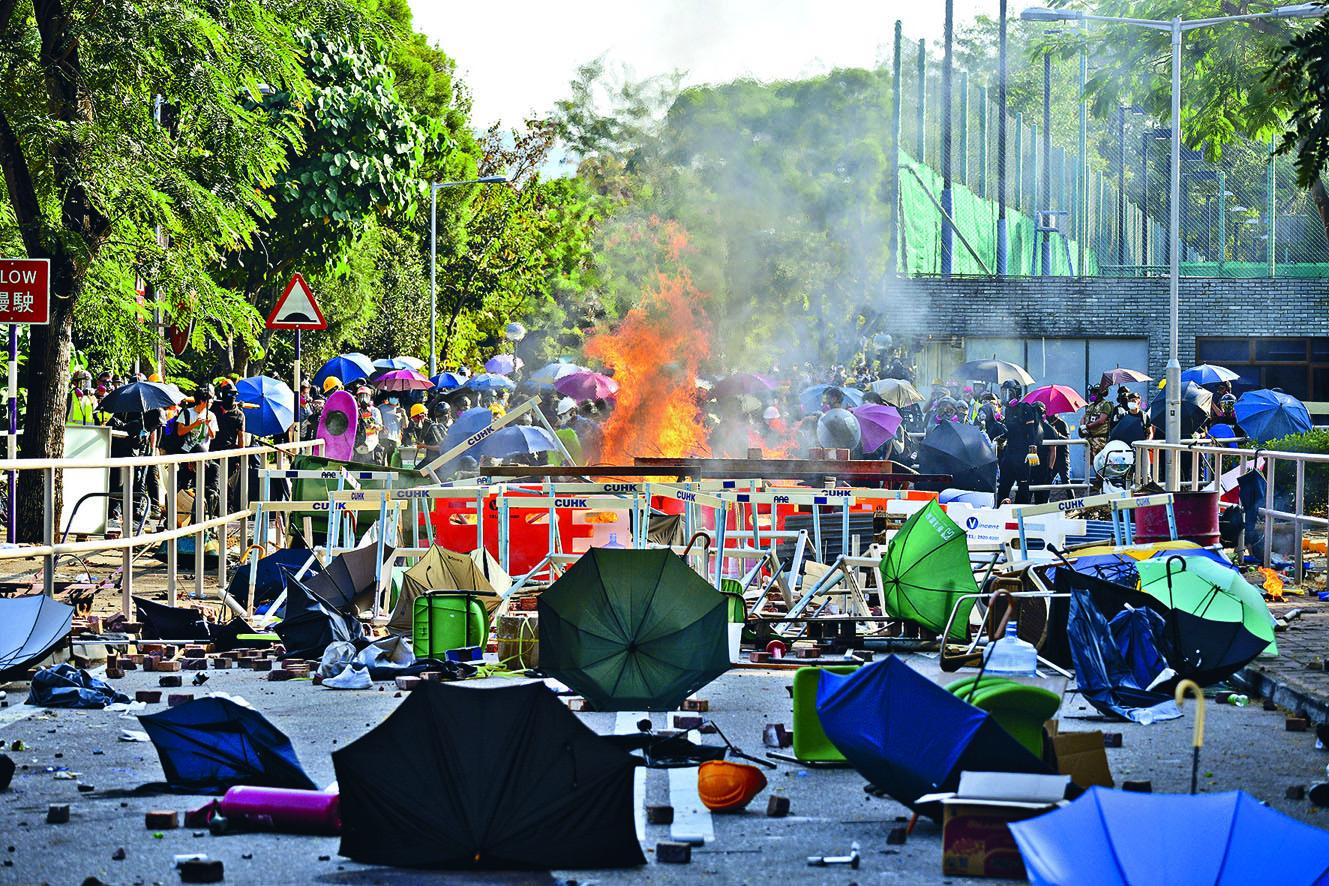 示威者用雨傘及雜物堵路,抵擋防暴警向中大校園推進。