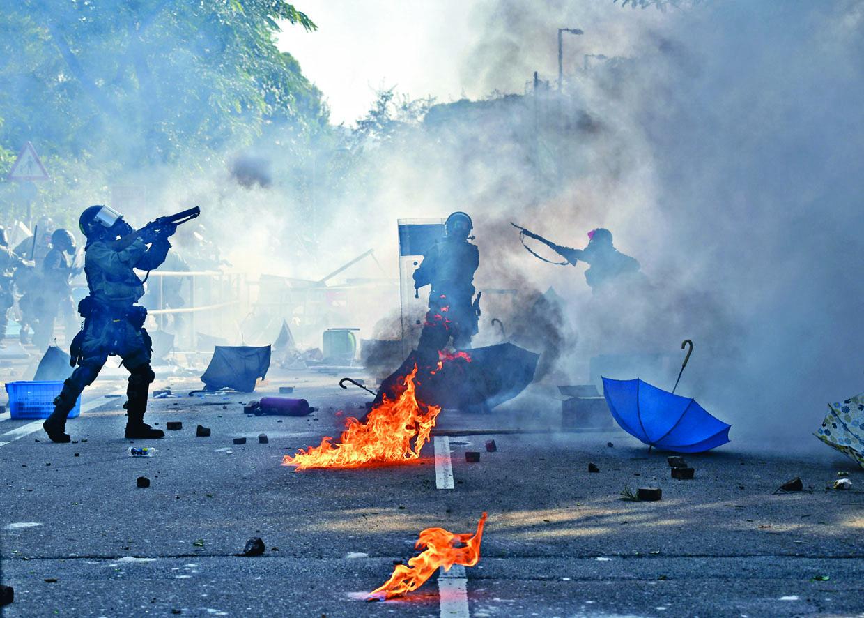防暴警發射催淚彈,驅散集結在中大二號橋示威者,地上汽油仍在燒。