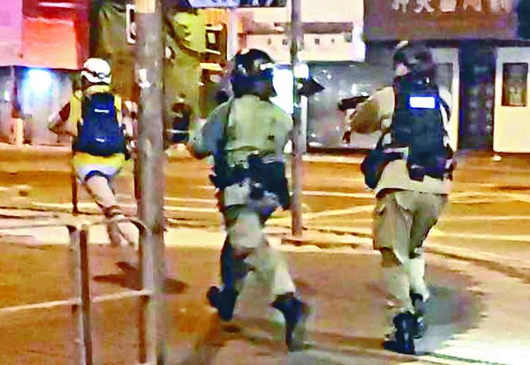 一名防暴警員(右)被指向商台記者(左)發射一枚海綿彈。