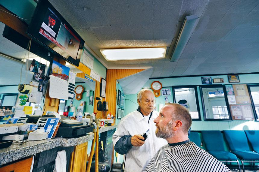 圖為緬因州波特蘭一名男子,當天在剪髮時抬頭收看電視報道首場彈劾公開聽證會。美聯社