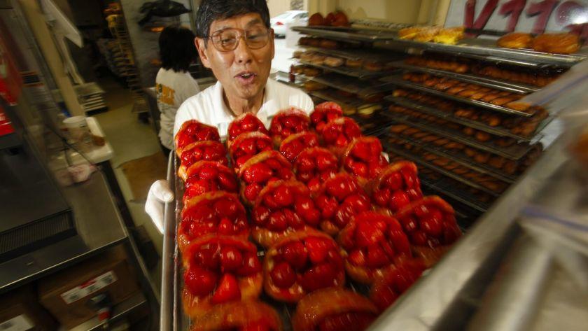 「Donut Man」創始人中野(Jim Nakano)於2011年端著一盤草莓甜甜圈。這家受到歡迎的商店將於明年擴展至大中央市場。洛杉磯時報