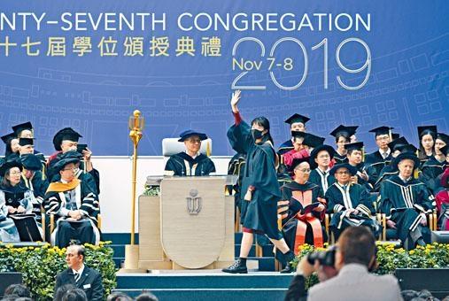 科大畢業生上台時戴口罩,向校長史維舉起「五大訴求」手勢。