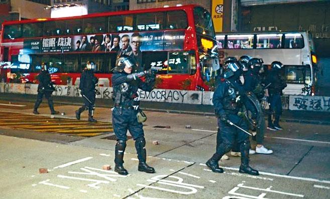 穿上保護裝備的探員遭示威者狂掟石,為自保向天鳴槍示警。