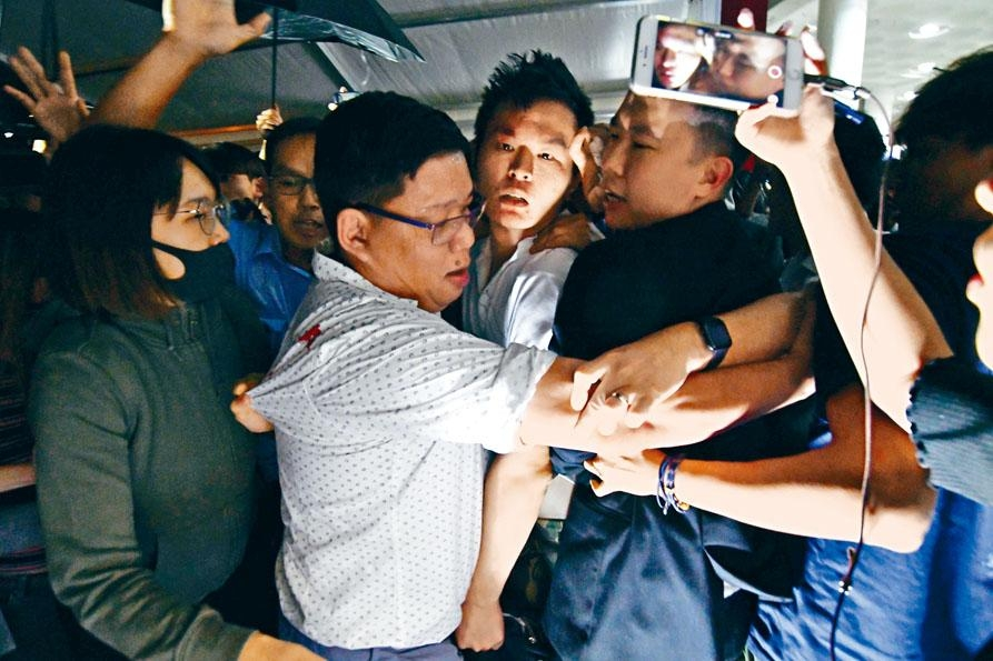 涉事內地生(中)被學生包圍,眼鏡被打至飛脫,額頭流血,在保安護送下往保安中心治理。