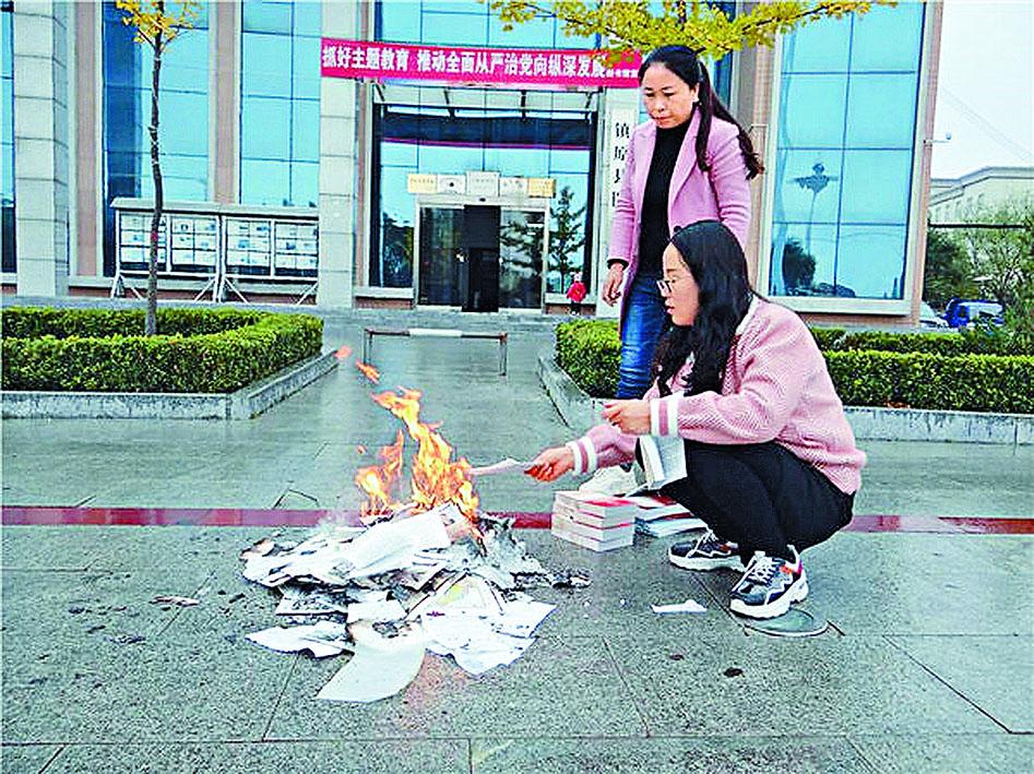 兩名工作人員在鎮原縣圖書館門口焚書。