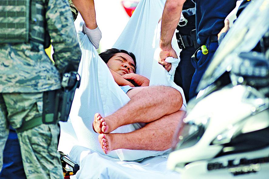 ■珍珠港美軍基地外,一名男 子周三被抬離現場。 美聯社