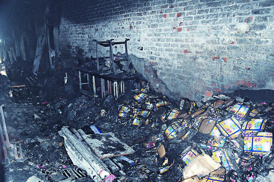 印度新德里發生大火的工廠內,可見被燒毀的大堆貨物。右圖可見大批民眾和記者聚集在火場外。 美聯社