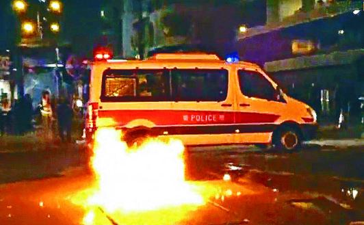 示威者在旺角向警車投擲汽油彈,越過車頂着地焚燒。