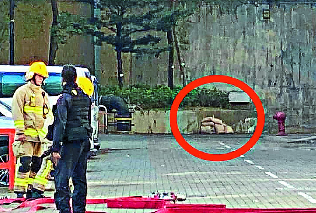 警方在危險品附近堆起沙包(圓圈示),準備引爆。