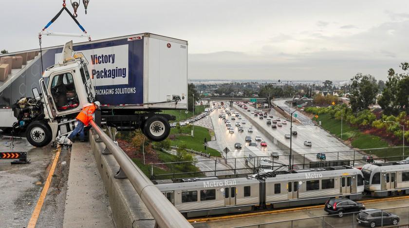一輛大型連結卡車在710號和60號高速公路交匯坡道上打滑,部分車體衝撞出柵欄,懸吊在連接橋上方。洛杉磯時報
