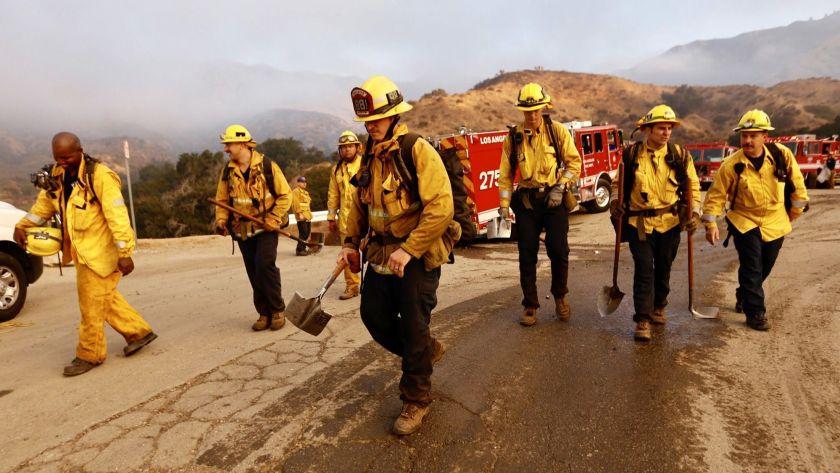 洛杉磯縣消防員2018年在秀瑪地區撲滅山火後準備返回車輛。洛杉磯時報