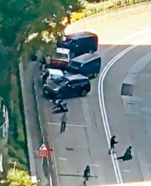 警方的客貨車及私家車,前後包抄截停載着疑匪的白色私家車和的士,探員制服疑匪按地上。