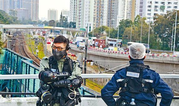 為防「三罷」行動影響列車,警方駐守天橋防拋雜物堵塞路軌。