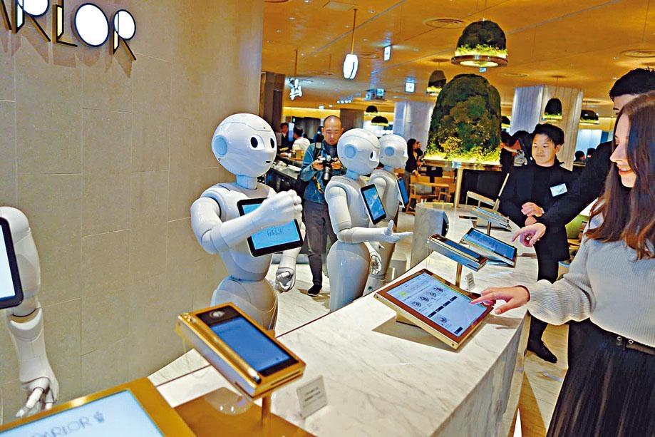 日本軟銀機械人公司在東京開設的機器人咖啡店昨日開幕,顧客向機械人員工落單。