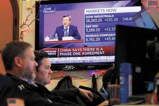 紐約交易所電視屏幕直播中國記者會宣布達成首階段貿易協議。美聯社