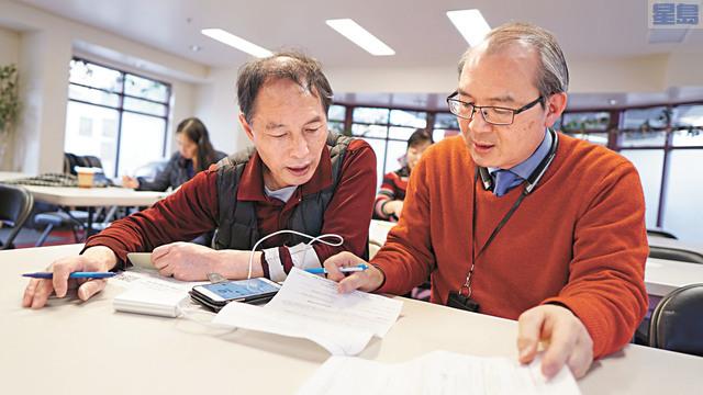 三藩市小商業發展中心顧問廖紀聖(右)協助華埠商戶填寫申報表。