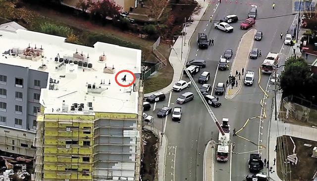 ■直升機上空拍攝現場,可見疑犯(紅圈)逃到屋頂,大批警員警車在樓下包圍現場。CBS電視畫面