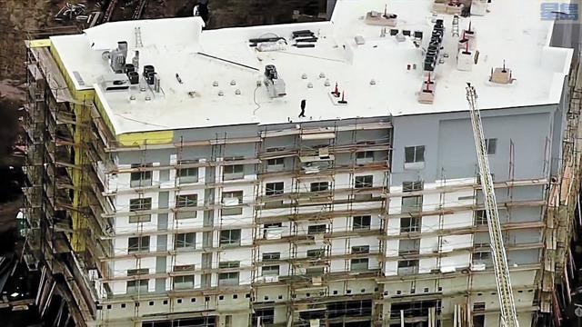 ■男子在樓頂多個小時未肯就範。CBS電視畫面