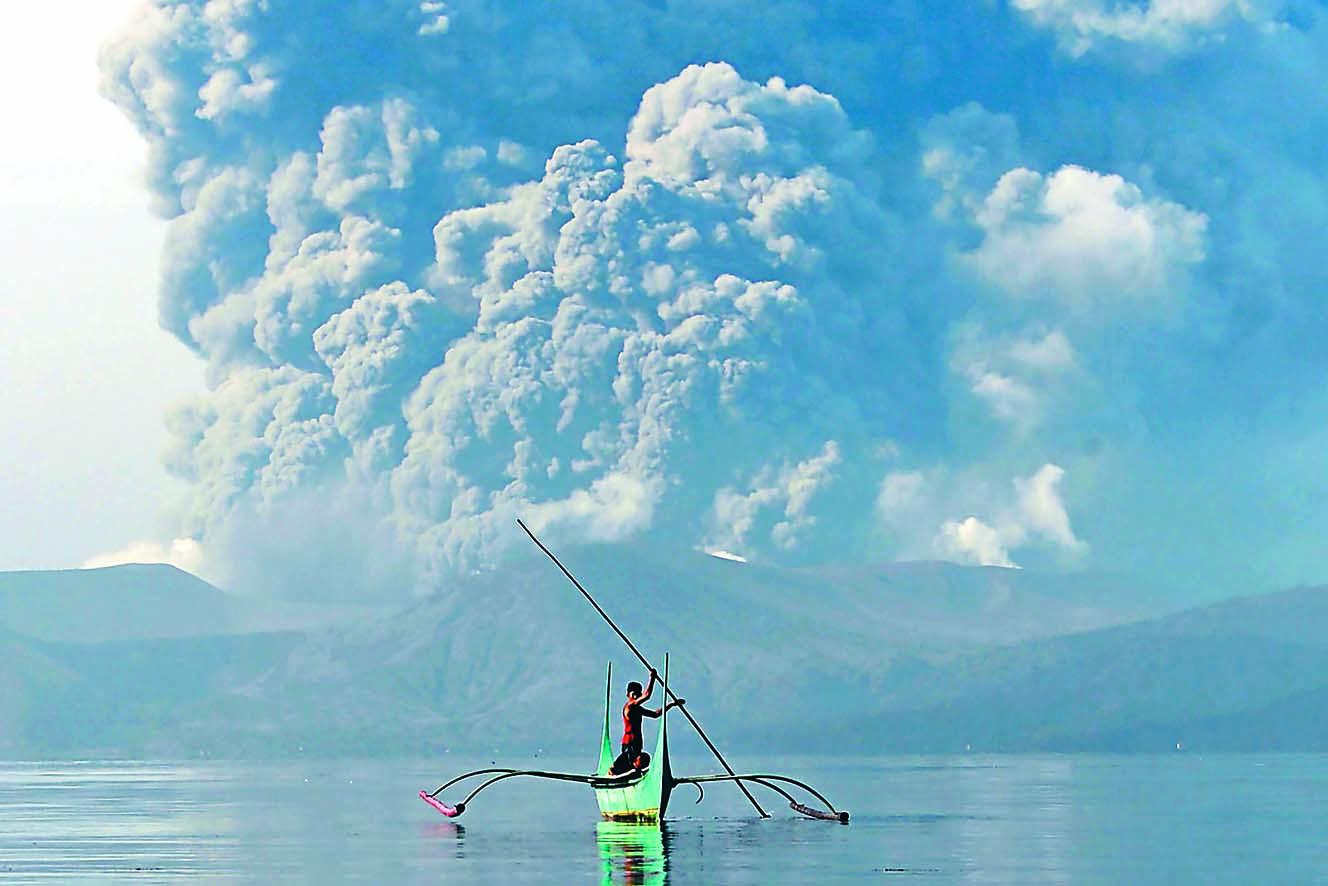 ■一名居住塔阿爾火山腳的 青年周一划獨木舟撤離,身 後火山灰瀰漫。 法新社