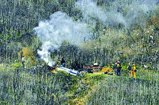 直升機墜毀後着火冒煙,消防員到場撲救。 美聯社