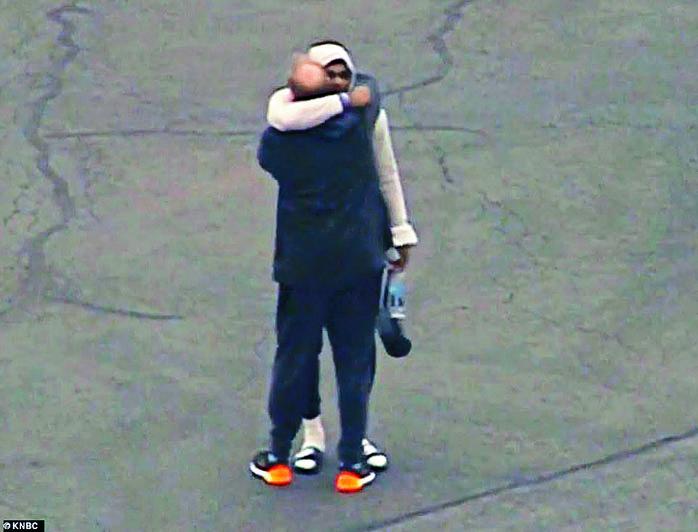 悲傷的勒邦占士(戴帽者)周日在機場擁着一名男子。 互聯網