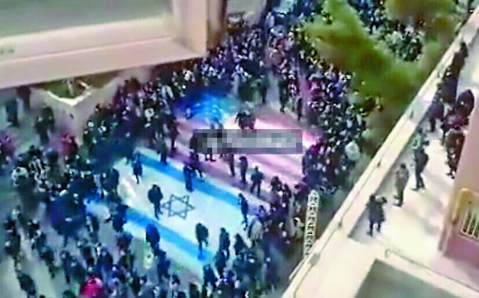 ■示威學生避免踩踏畫在沙希德.貝赫什提大學 門外的美、以國旗。  互聯網