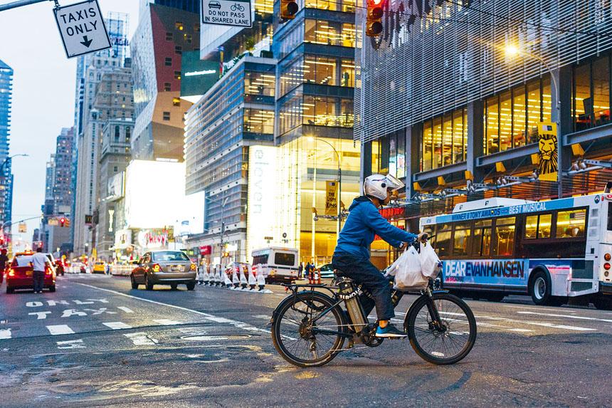 一名外賣郎騎著電動單車在曼哈頓送外賣。 Mark Abramson/紐約時報