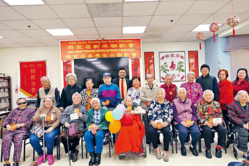 25區區長盧漢士(後左5)向樂宜居老人大廈的長者送上鼠年新春祝福與為冬季生日的壽星慶生。梁敏育攝