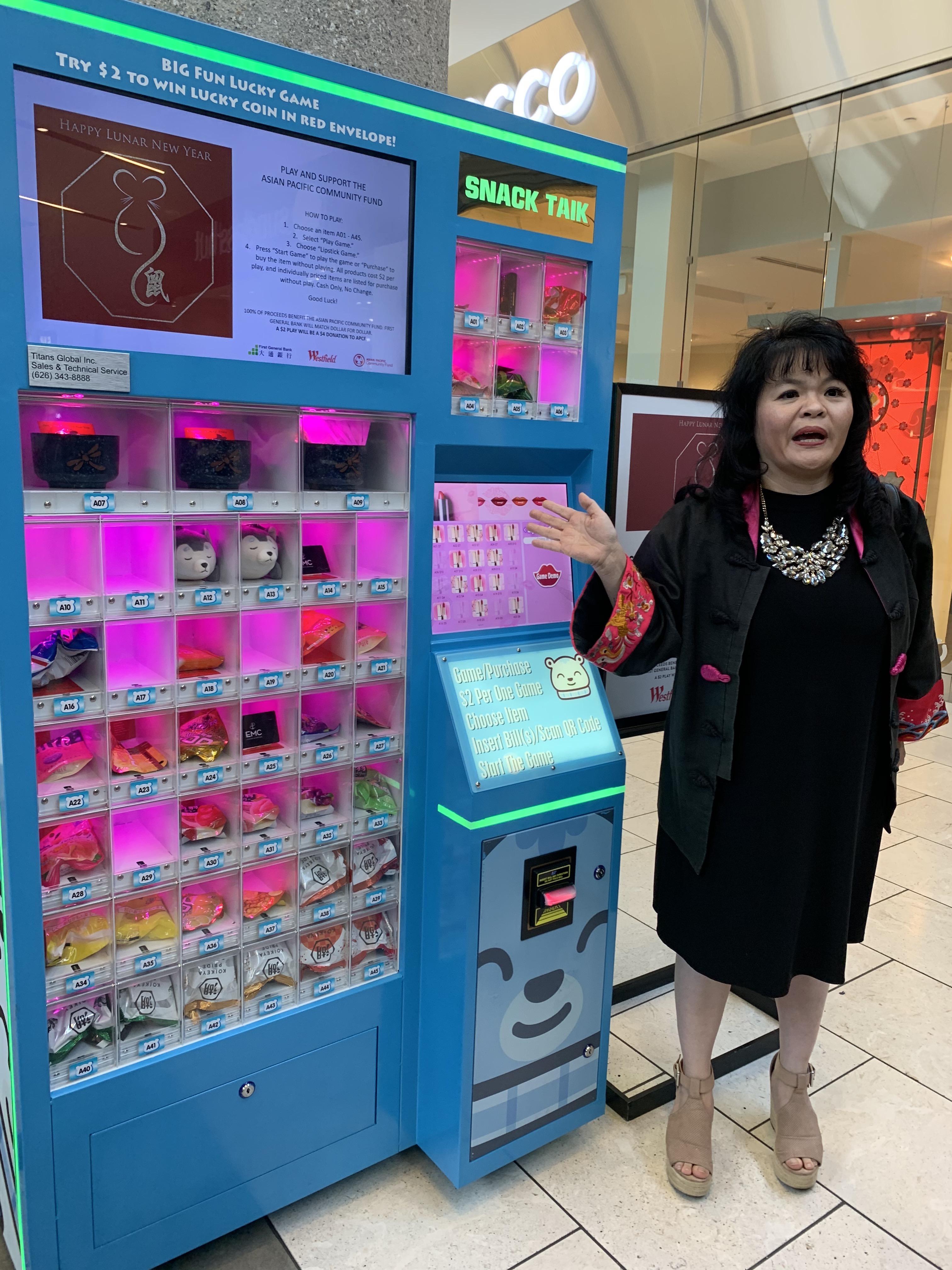 亞太社區基金會執行長黃群雁向民眾介紹特色「扭蛋機」以籌善款。記者華夏美佳攝。