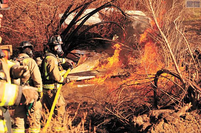 消防隊員在撲滅火焰後發現了飛機上的四名死者,屍體有嚴重燒傷。洛杉磯時報圖