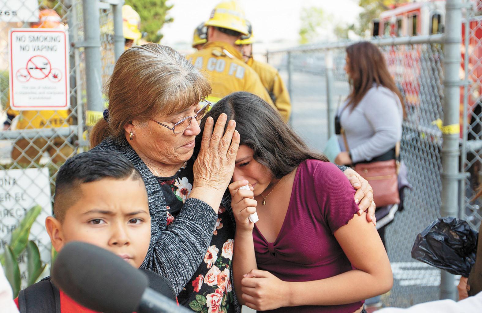 飛機燃料掉落在學校,致地面多人受傷。圖為家長安慰受到驚嚇的孩子。美聯社