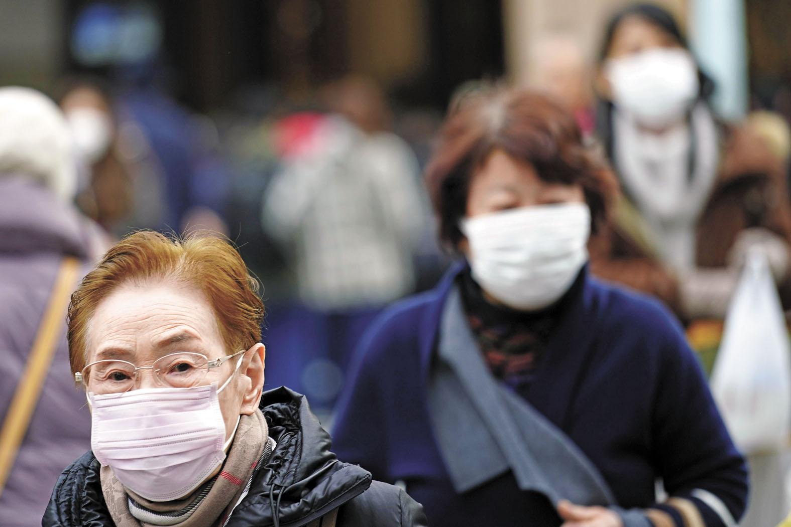 在日本東京,民眾戴著口罩穿過購物區。美聯社