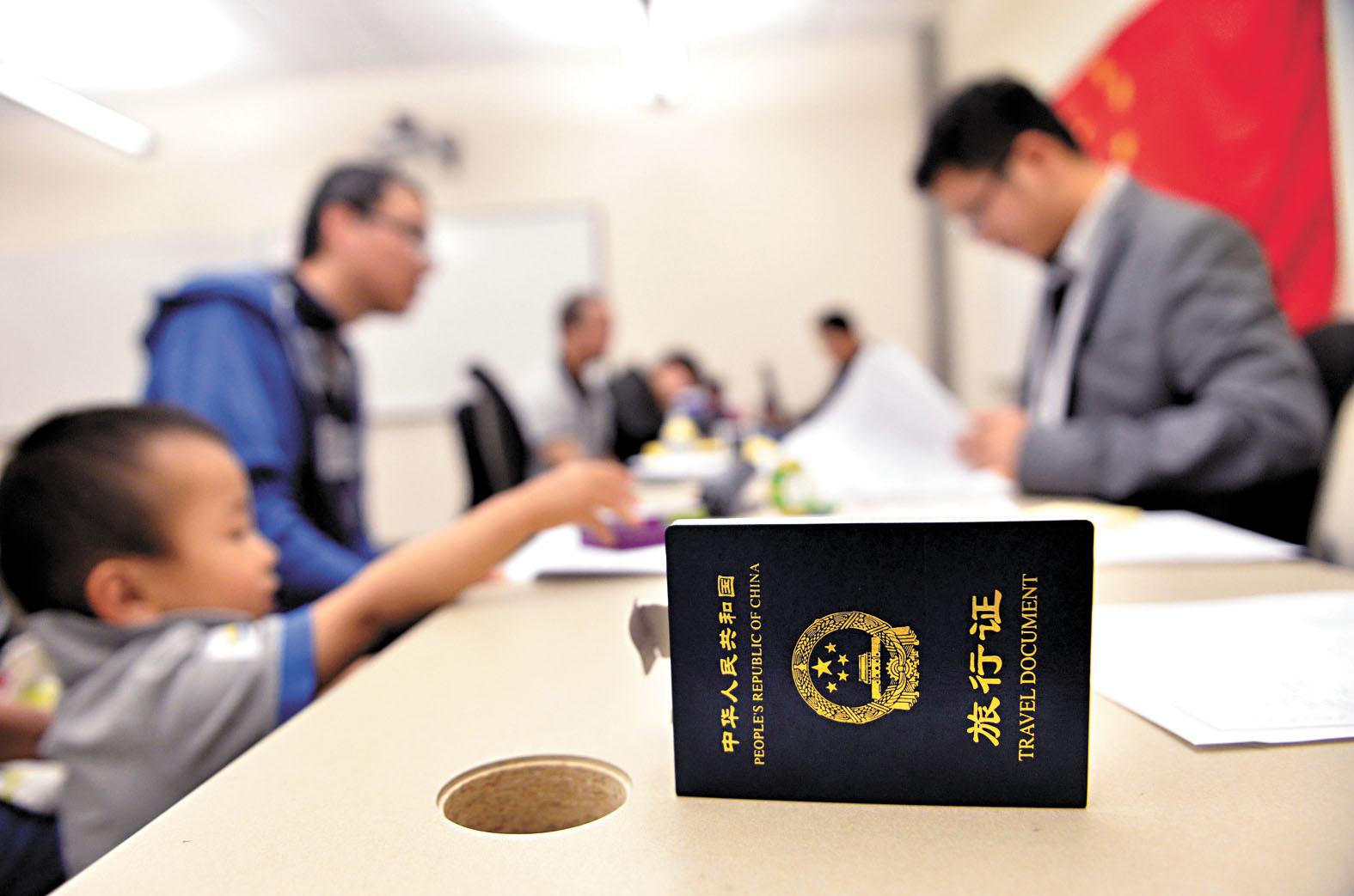 中國各駐外使領館將於2月起實施便民舉措,實現護照(小圖)「全球通辦」,圖為中國駐美大使館領事人員給申請人辦理證件。新華社資料圖睛