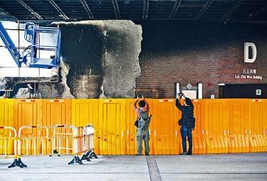 D座大樓外牆紅磚牆剝落,被黃色水馬圍封。