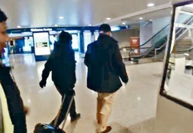 季炳雄(右)與一名替他拖篋的洋漢交談數句後,突急步前行。