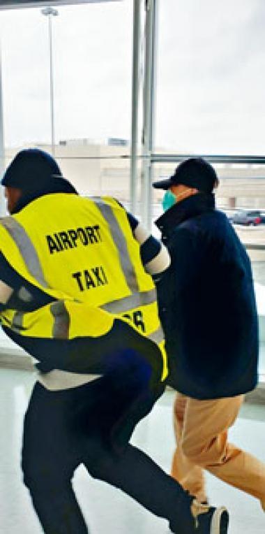 身穿黃色機場的士背心的洋漢突然拉着季炳雄(右),加快步伐圖擺脫記者。