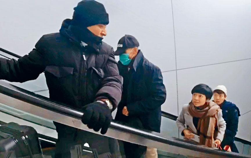 接機男子一前一後,帶着季炳雄(左二)乘扶手電梯前往停車場。