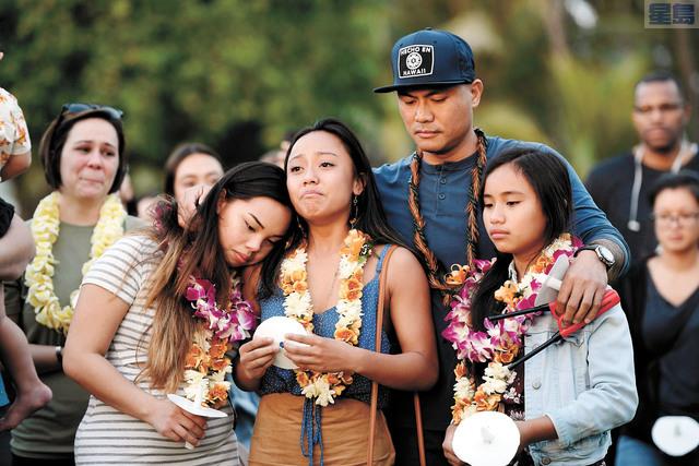 其中一名遇害警員恩里克斯的前夫John Enriquez(中右)與三名女兒21日出席追悼活動。Bruce Asato/Honolulu Star-Advertiser/美聯社