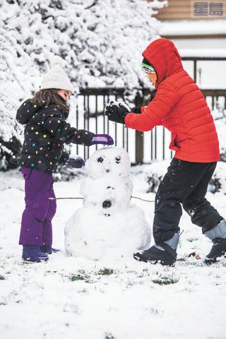下雪不用上課,Shoreline市的小朋友開心堆雪人。Steve Ringman/西雅圖時報/美聯社