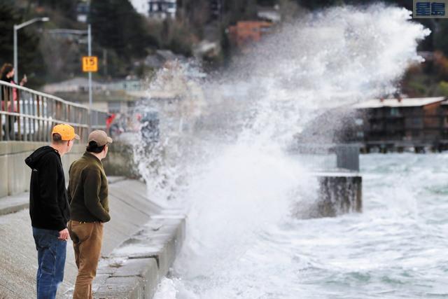 西雅圖地區本周迎來冬季風暴,圖為民眾觀看沿岸激起的巨浪。美聯社