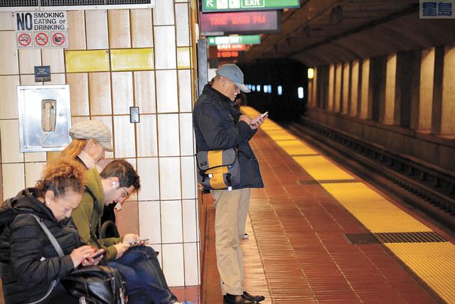 去年捷運手機搶劫案超過一千宗。圖為米慎24街捷運站月台上民眾使用手機。記者賴漢鈞攝