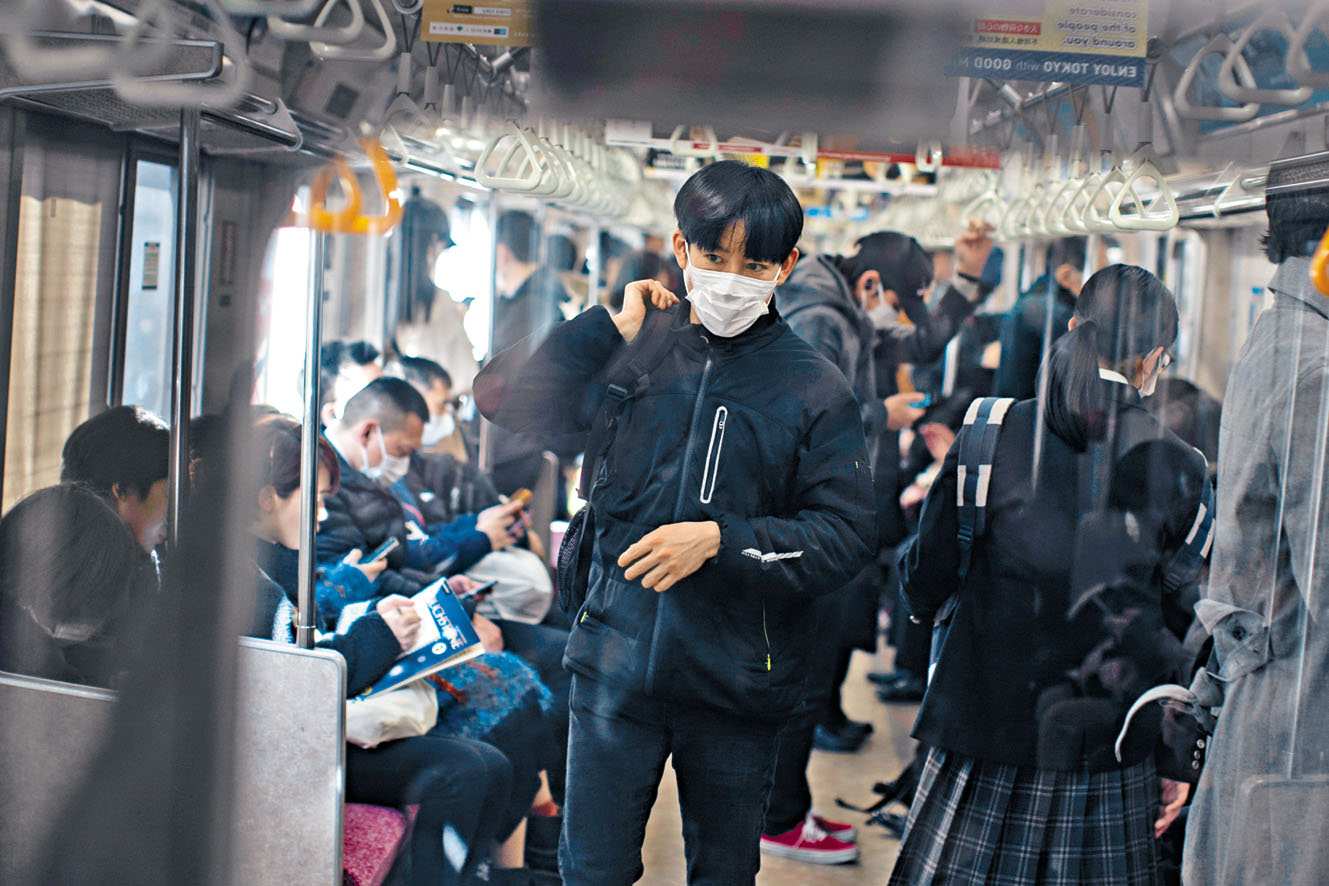 乘客周一在東京戴着 口罩乘搭列車。 路透社