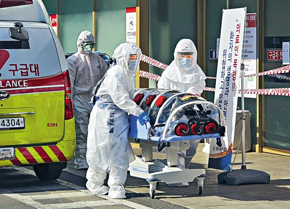 穿着全套保護裝備的南韓醫護人員,周三將一名疑似新冠肺炎患者送往大邱市一所醫院。 美聯社