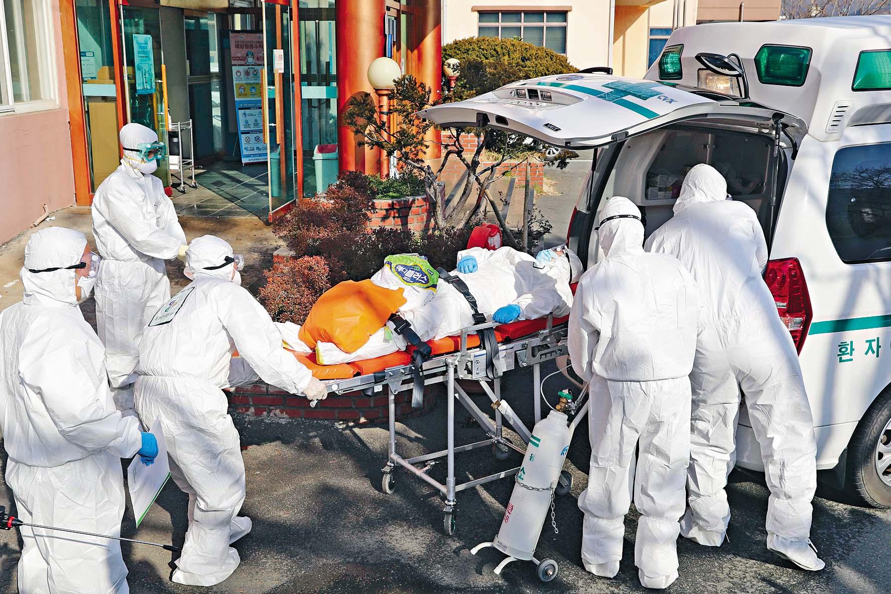 清道郡穿着防護裝備的醫務人員,昨日將一 名疑似新冠肺炎患者送上救護車轉院。 法新社