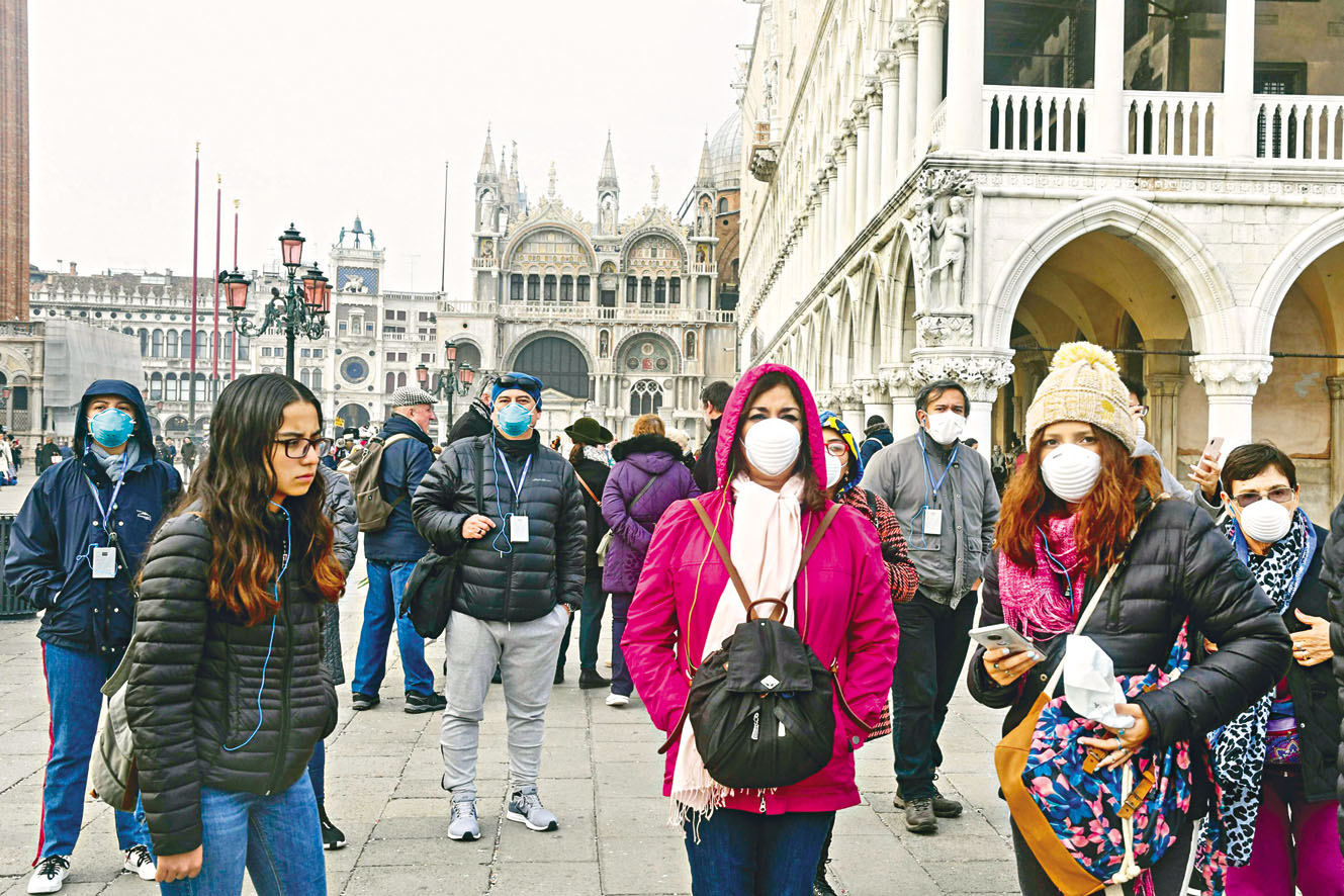 意大利威尼斯狂歡節今年因 新冠肺炎取消。圖為戴口罩的 遊客周二在市內遊覽。 法新社